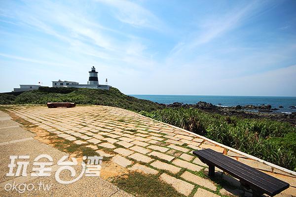 坐在燈塔附近的平台上,可以遠眺燈塔和海洋/玩全台灣旅遊網攝