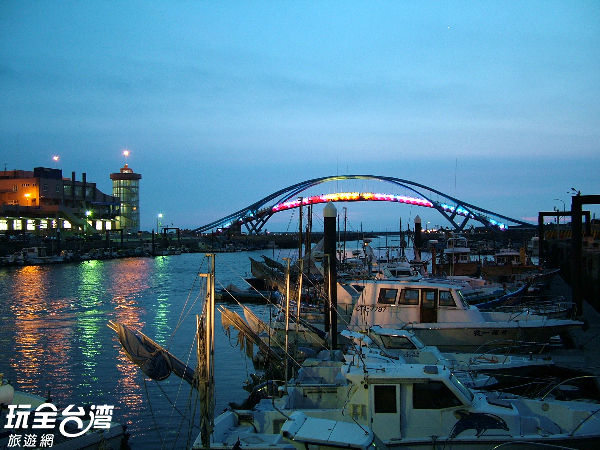夜晚的漁港在觀海橋燈光的投射下,更顯浪漫美麗。/玩全台灣旅遊網攝
