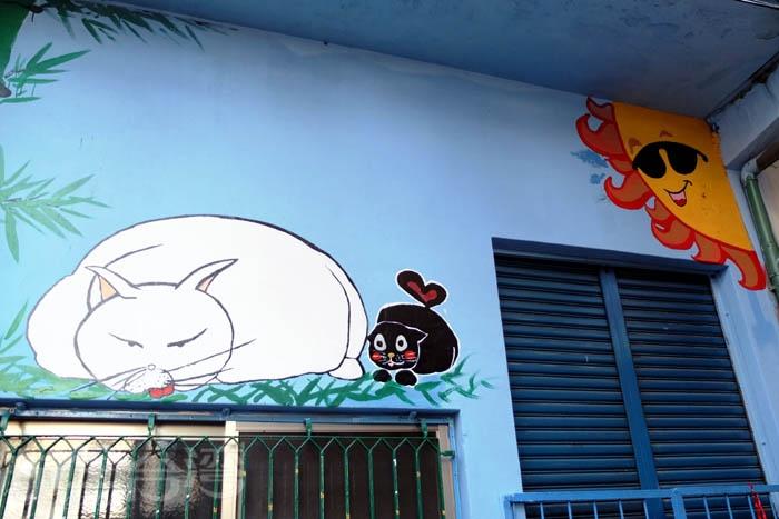 :一隻小黑貓愛慕著那隻慵懶的大肥貓,這兩隻貓正窩在一塊兒曬日光浴,走在貓巷裡每幅畫作都讓人很自然會發揮想像力看圖說故事呢!/玩全台灣旅遊網特約記者阿辰攝