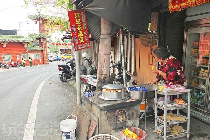 簡陋小攤子前擺著一座很有年份的古早爐灶,燒著柴火熬煮茶葉蛋,吸引饕客聞香上門。/玩全台灣旅遊網特約記者阿辰攝