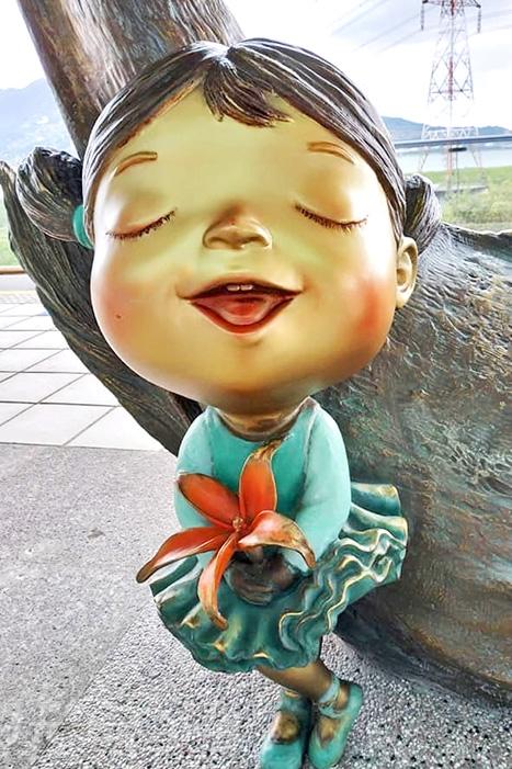 手裡拿著美麗小紅花兒的閉眼可愛小女孩。/玩全台灣旅遊網特約記者隱月攝